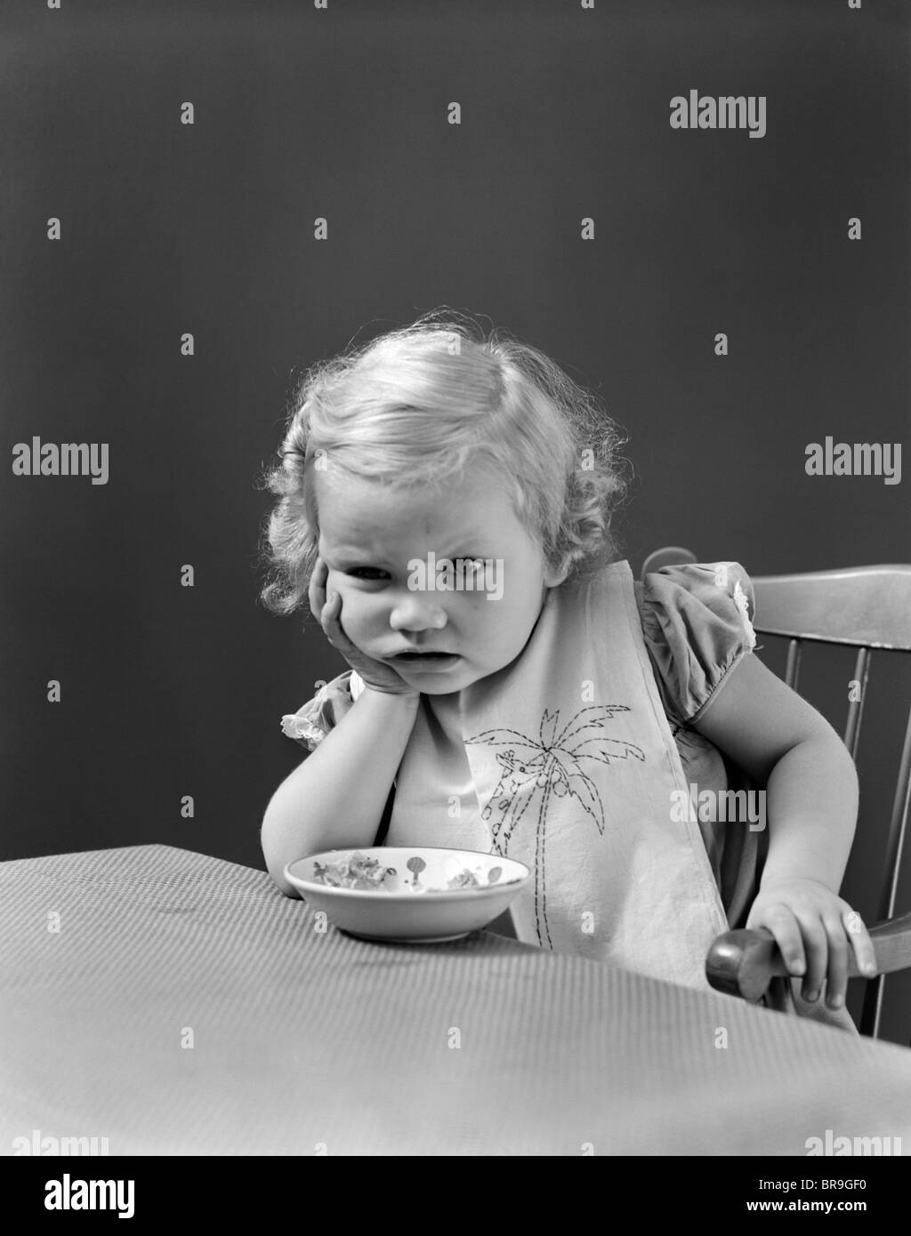 Années 1930 Années 1940 TRISTE FILLE BÉBÉ À TABLE AVEC BOL DE CÉRÉALES Photo Stock