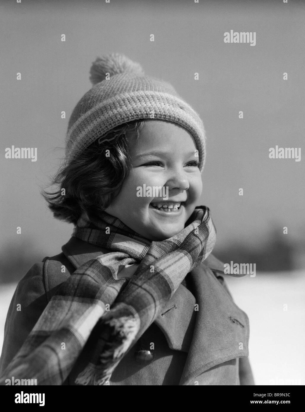 1930 SMILING LITTLE GIRL WEARING HAT VÊTEMENTS D'HIVER ROBE FOULARD Banque D'Images
