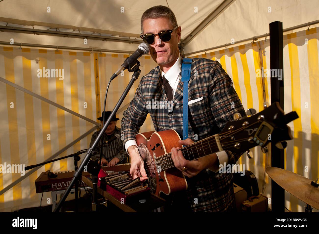 Un homme portant des lunettes de lecture d'une guitare acoustique semi dans un groupe, UK Photo Stock