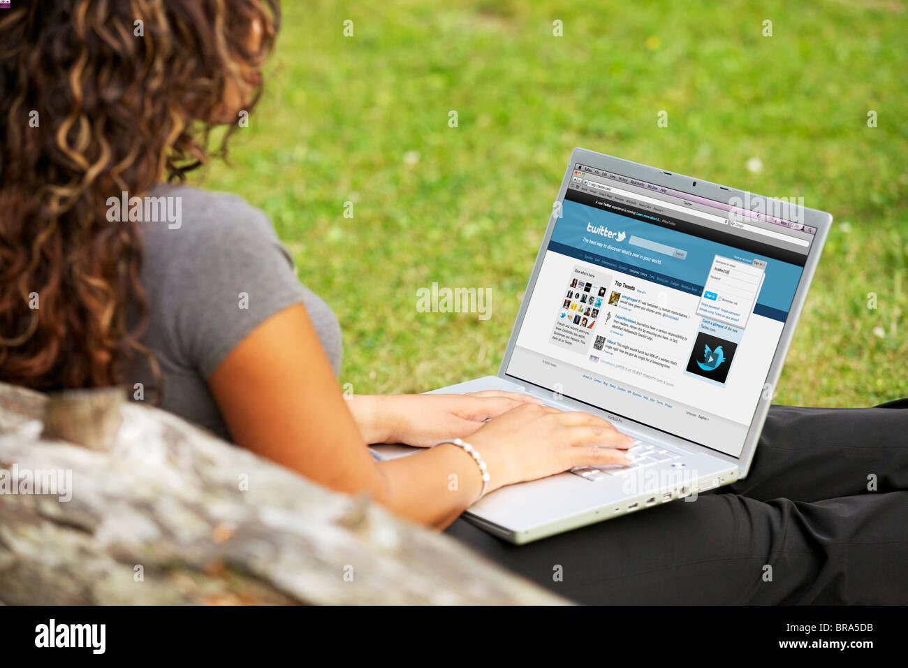 Jeune femme en signature sur sa page Twitter en ligne sur un seul ordinateur portable au parc Photo Stock