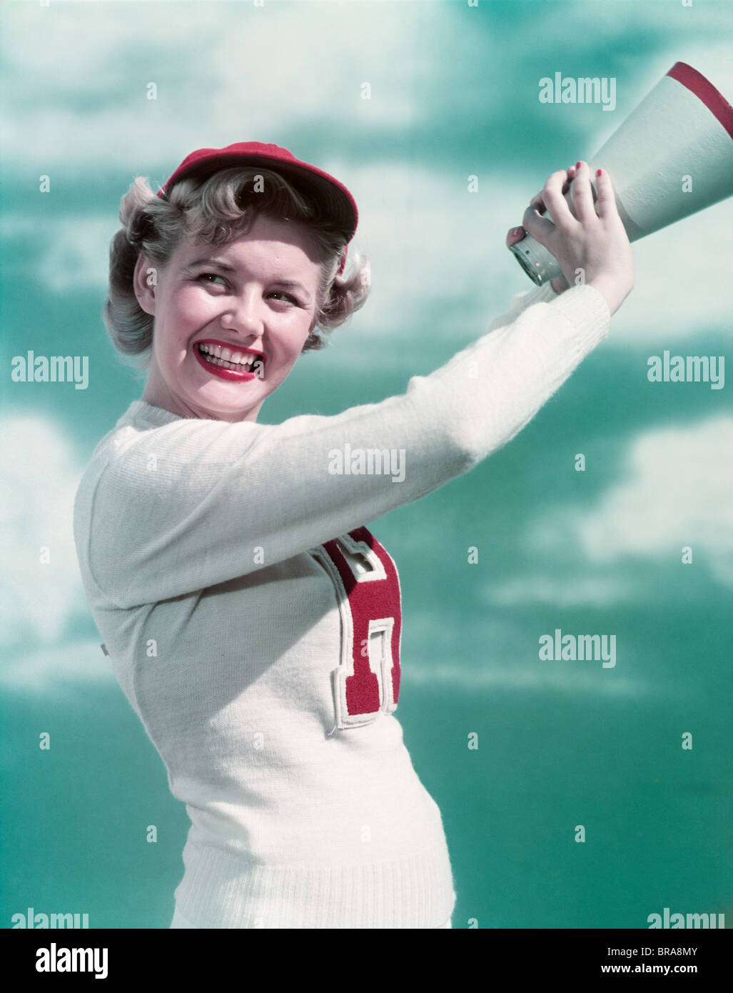 Années 1940 Années 1950 SMILING WOMAN WEARING CHEERLEADER LETTRE VARSITY SWEATER POINTING Photo Stock