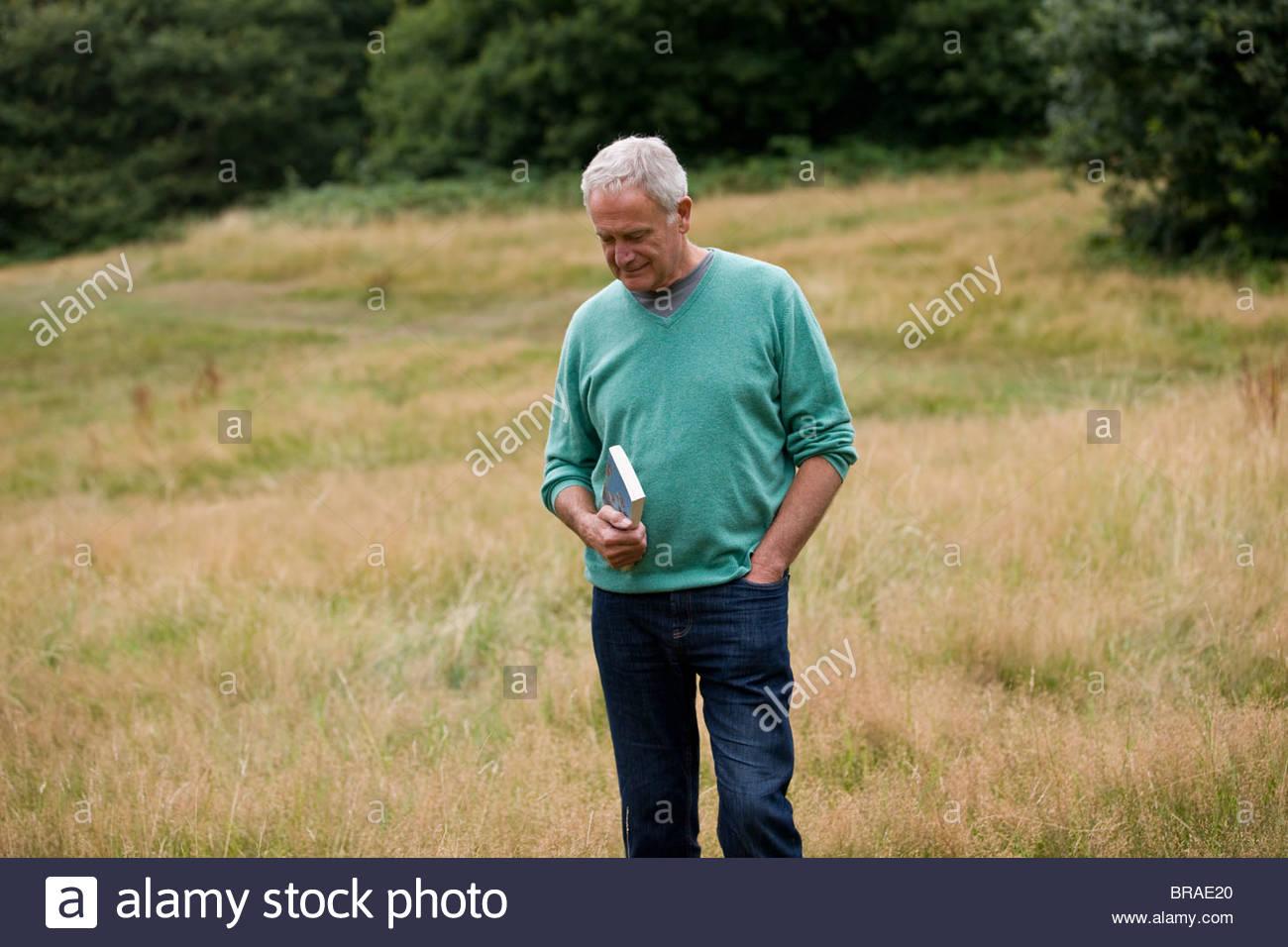 Un homme debout dans un champ, tenant un livre Photo Stock