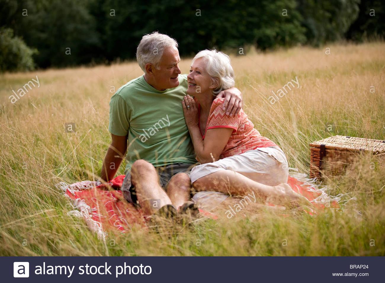 Un couple assis sur une couverture, embracing Photo Stock
