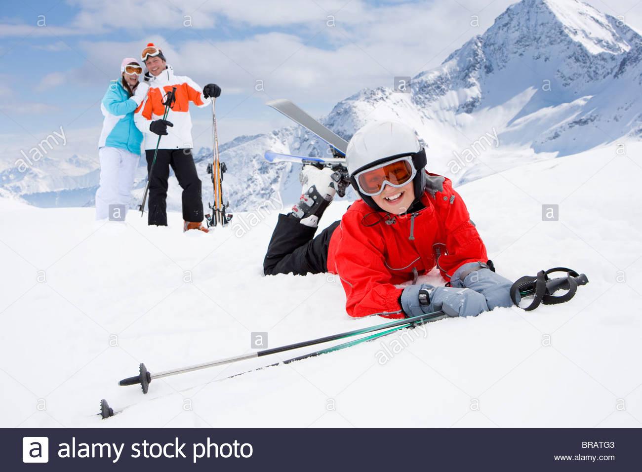 Garçon sur des skis de neige en baisse tandis que les parents watch Photo Stock