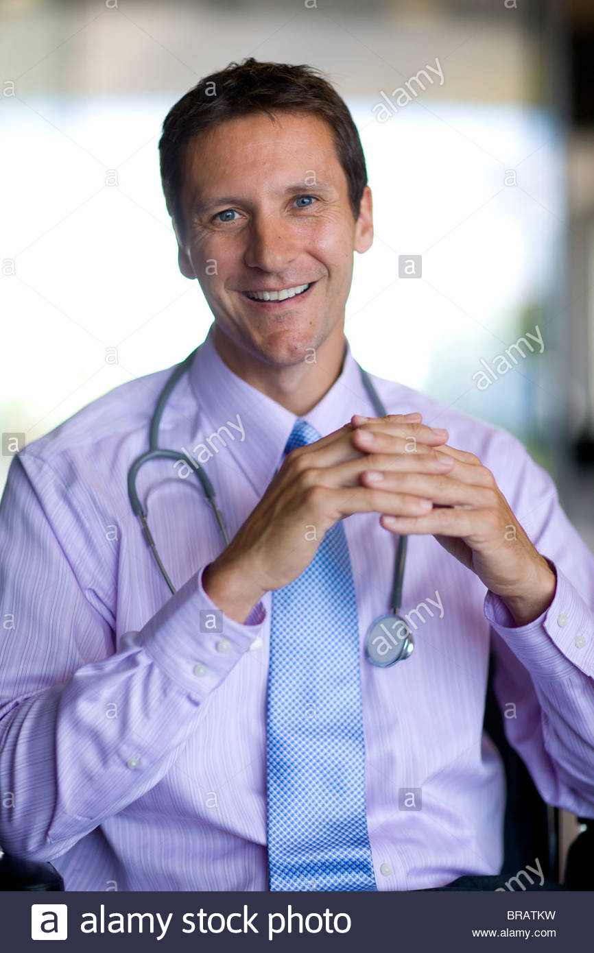 Smiling doctor with stethoscope and hands clasped Photo Stock