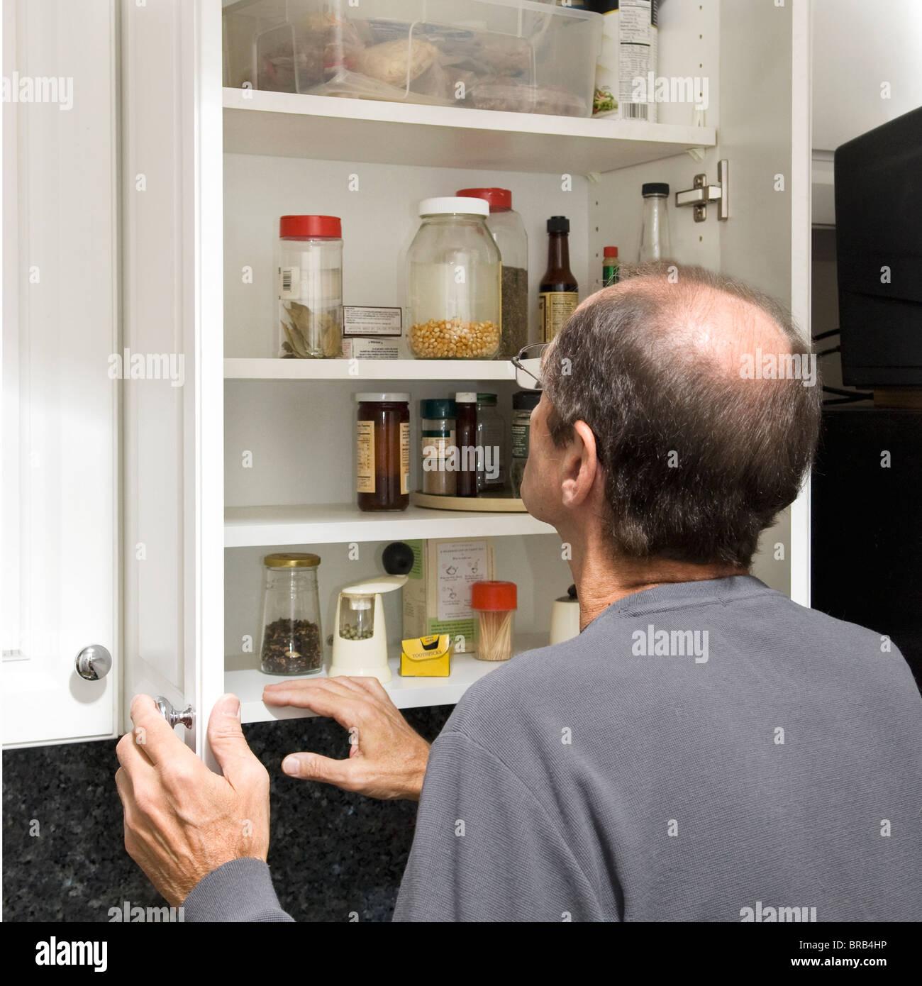 Homme debout en face de l'armoire de cuisine avec peu de nourriture Photo Stock