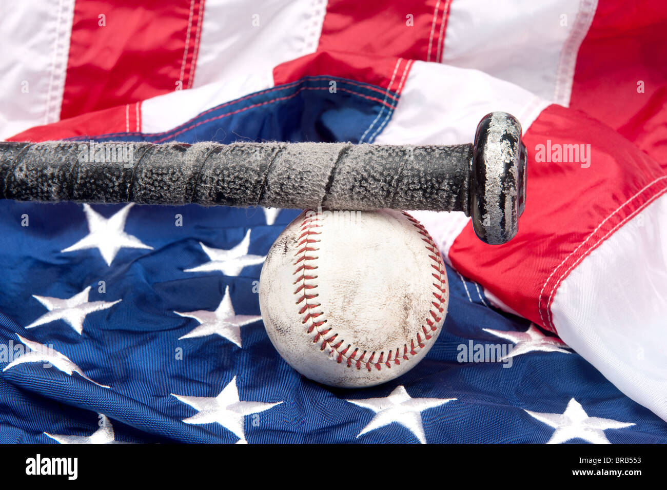 L'équipement de base-ball y compris une batte et une balle de baseball sur un drapeau américain. Photo Stock