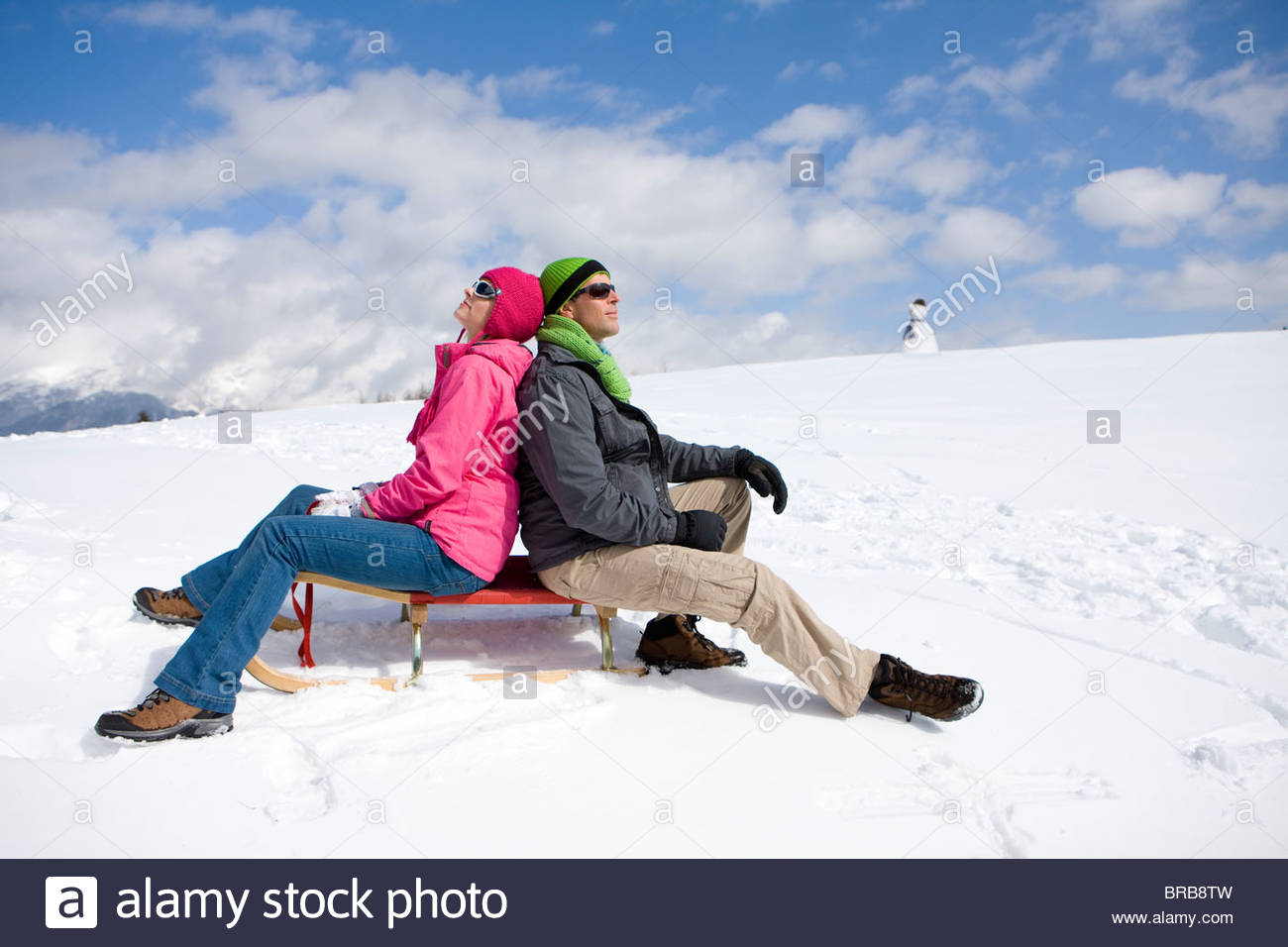 Smiling couple assis sur un traîneau sur la pente de ski enneigées Photo Stock