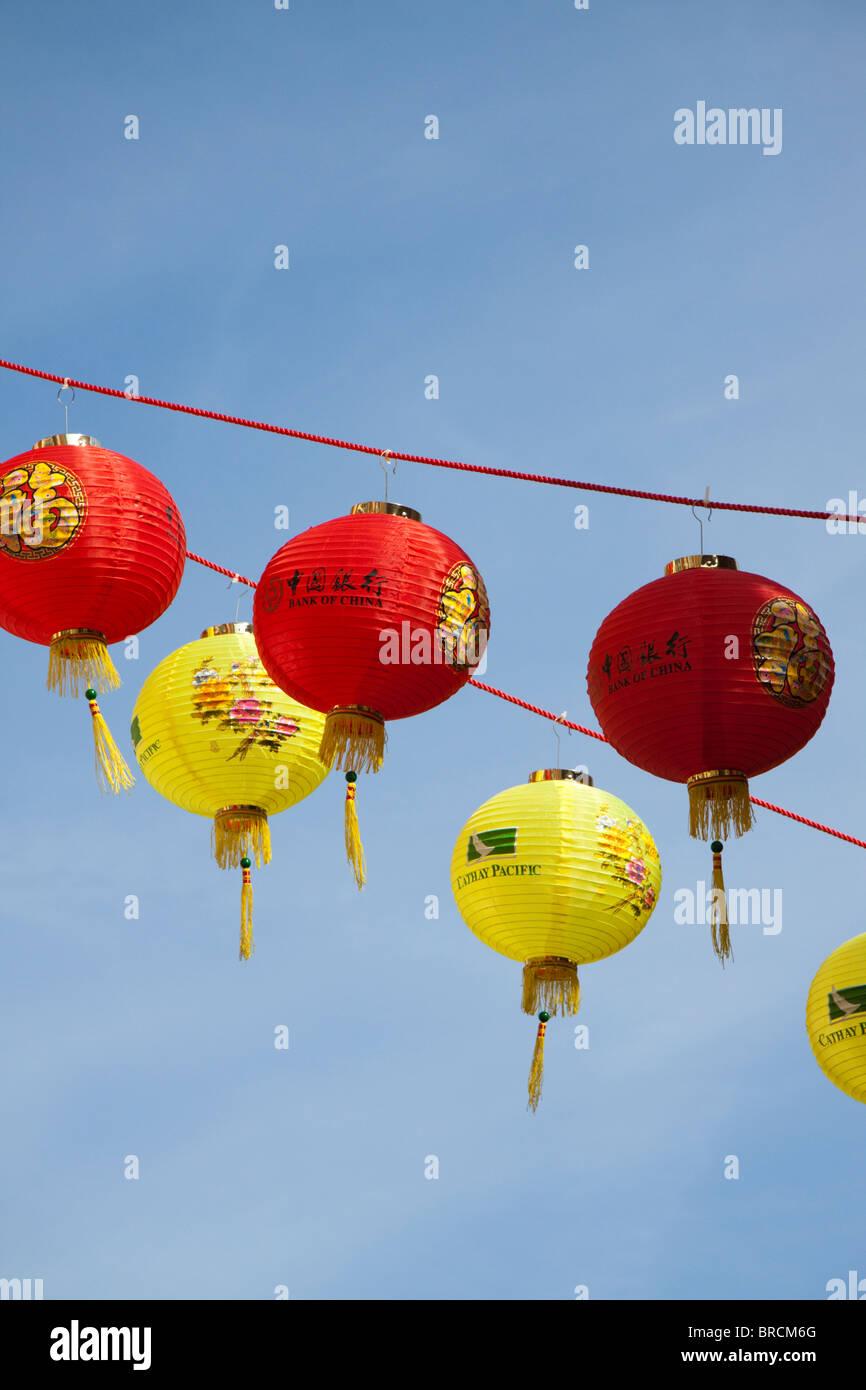 Le rouge et jaune lampions hanging against a blue sky Photo Stock
