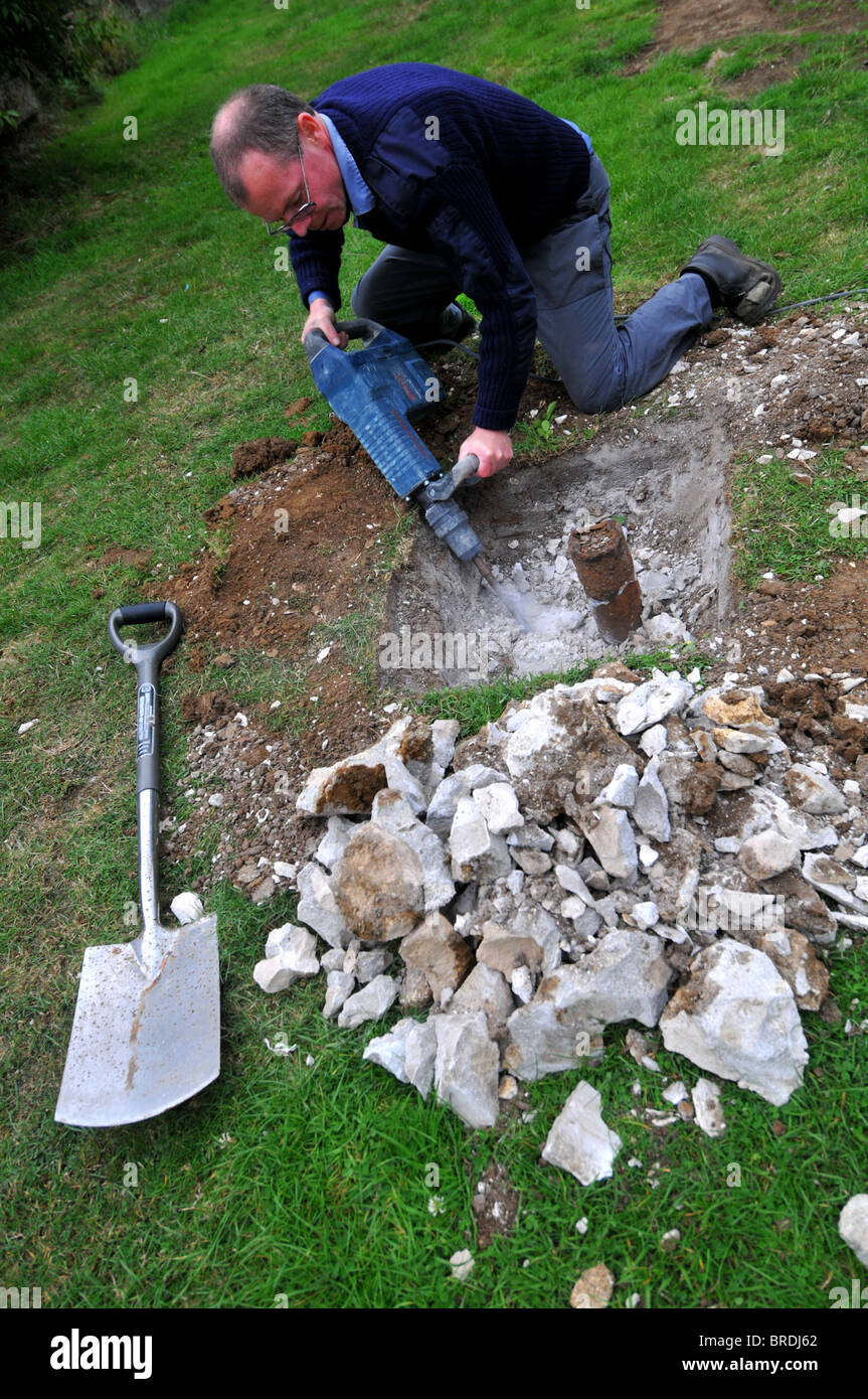 Marteau-piqueur, l'homme à l'aide d'un marteau pneumatique ou jackhammer outil pour liquidation Photo Stock