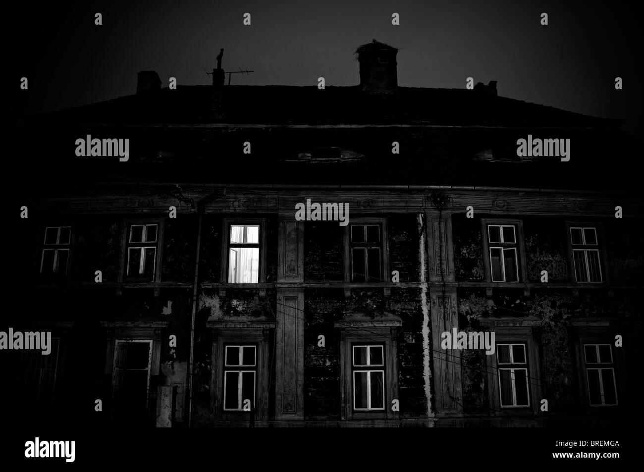 Roumanie, Sibiu. La lumière d'une fenêtre d'une ancienne maison la nuit Photo Stock