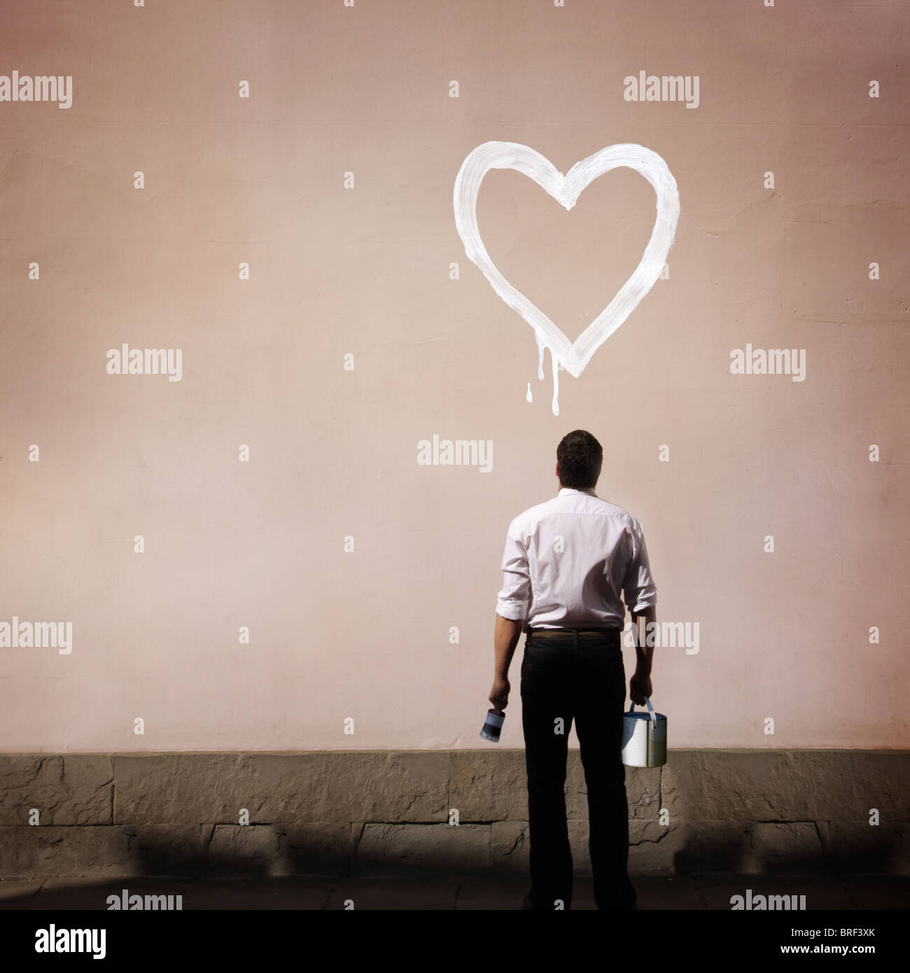 Homme avec coeur peint sur mur Photo Stock