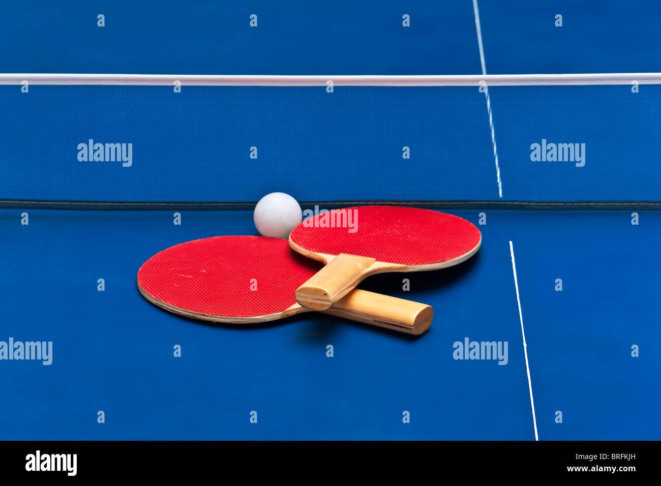 Paire de raquettes de tennis de table au-dessus d'un terrain de jeu bleu Photo Stock