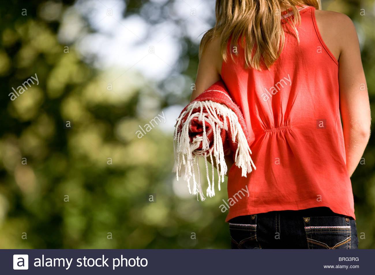 Une jeune fille portant une couverture de pique-nique, close-up Photo Stock