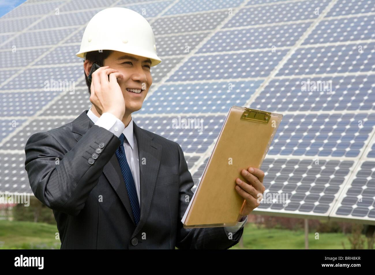 Portrait d'un ingénieur en face de panneaux solaires Photo Stock