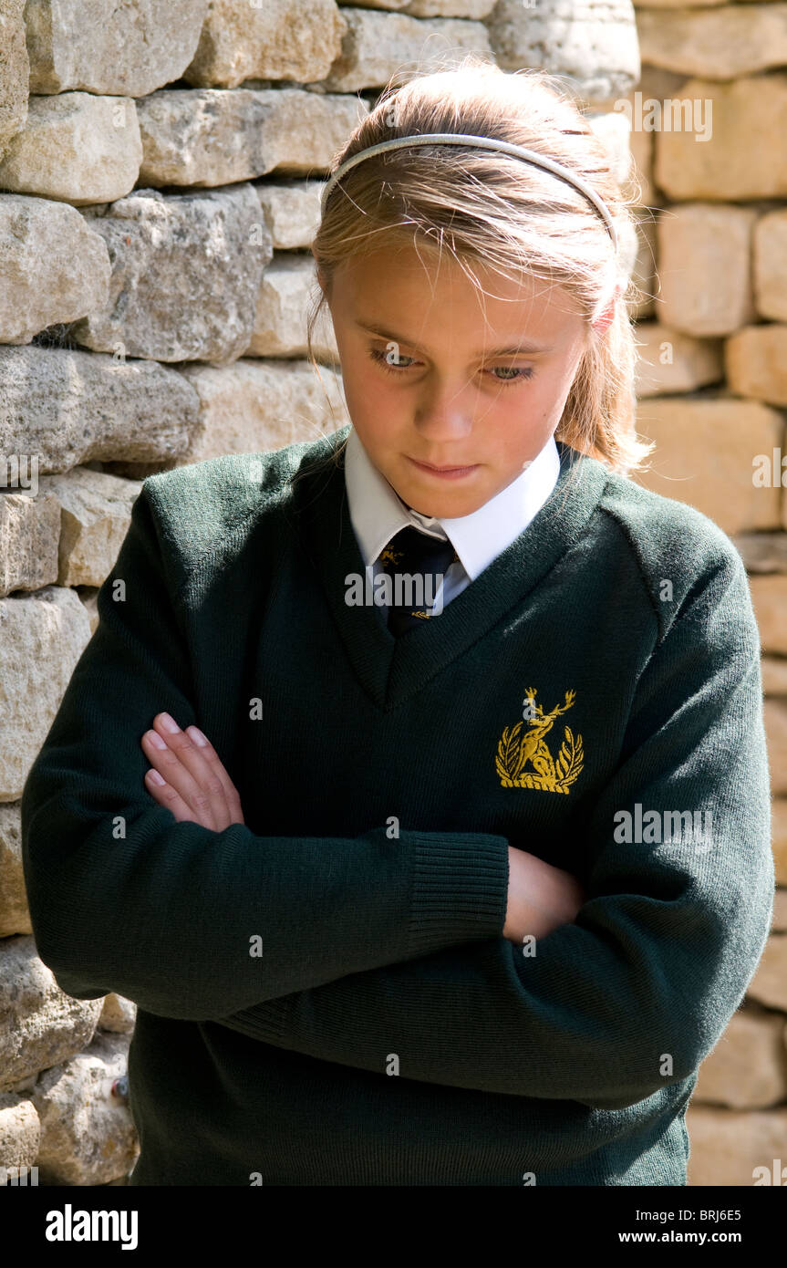 Écolière avec bras croisés portant l'uniforme scolaire à la malheureuse vers le bas Photo Stock