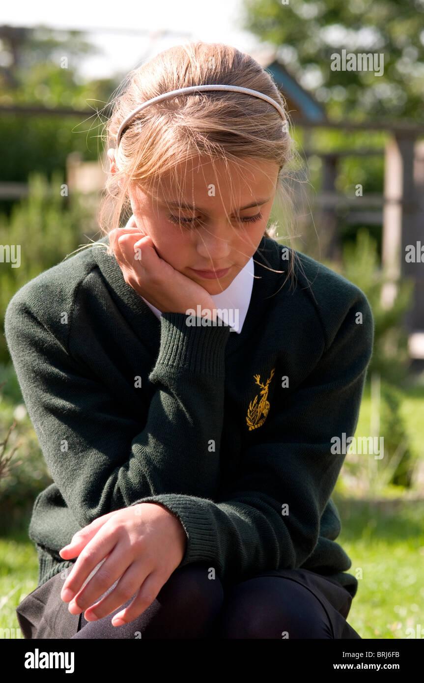 Écolière avec tête appuyée sur sa main à la recherche vers le bas et assez Photo Stock