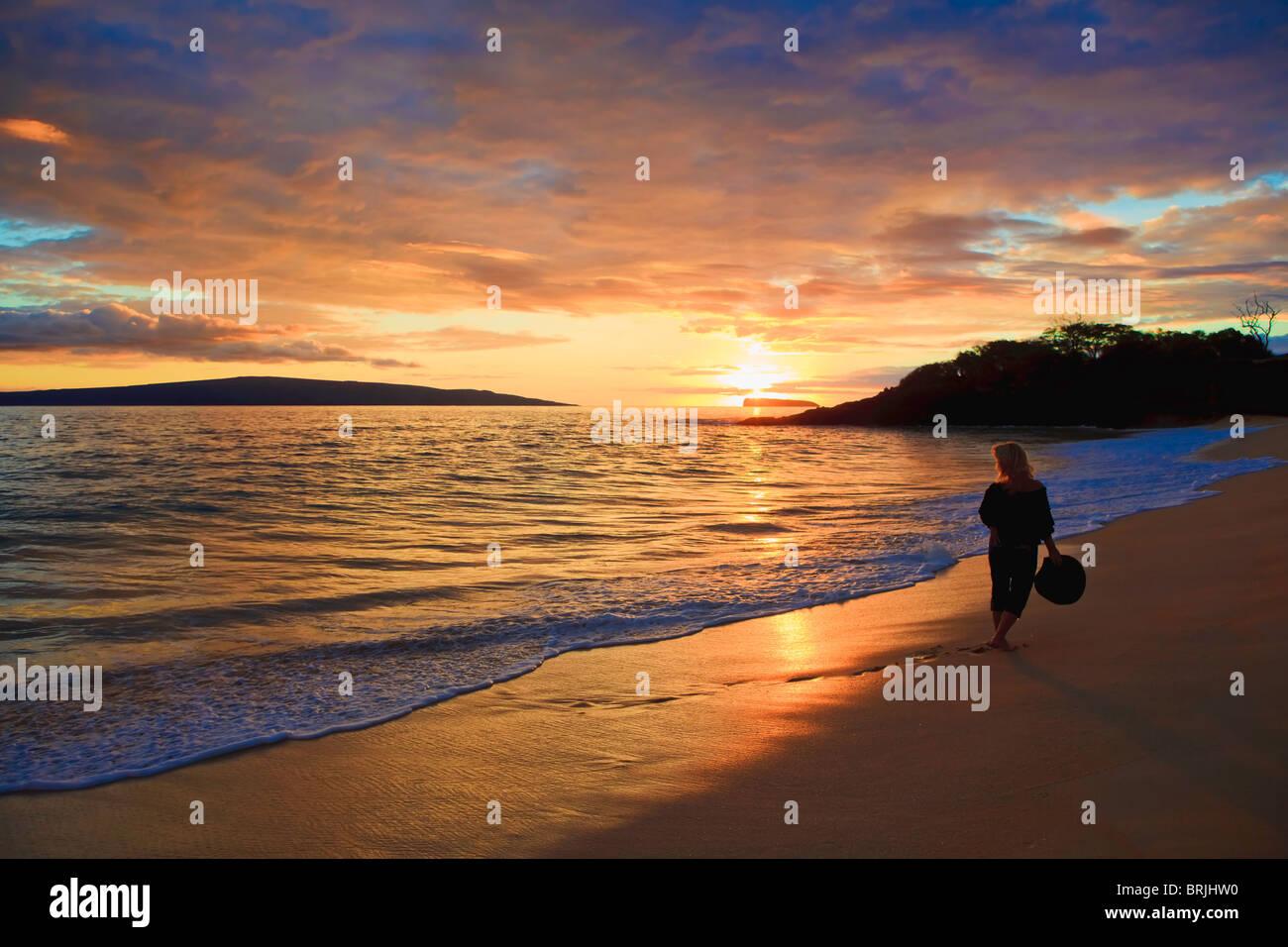 Beau moyen age femme marche sur la rive seule sur la plage de Maui Makena, au coucher du soleil Photo Stock