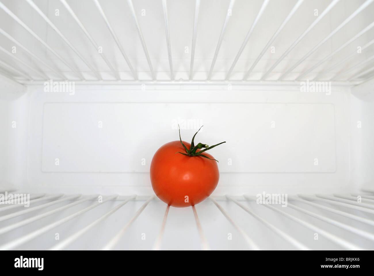 Tomate rouge unique assise sur la durée de l'intérieur de réfrigérateur Photo Stock