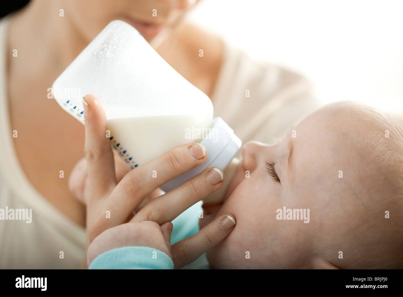 Boire du lait pour bébé à partir de la bouteille Photo Stock