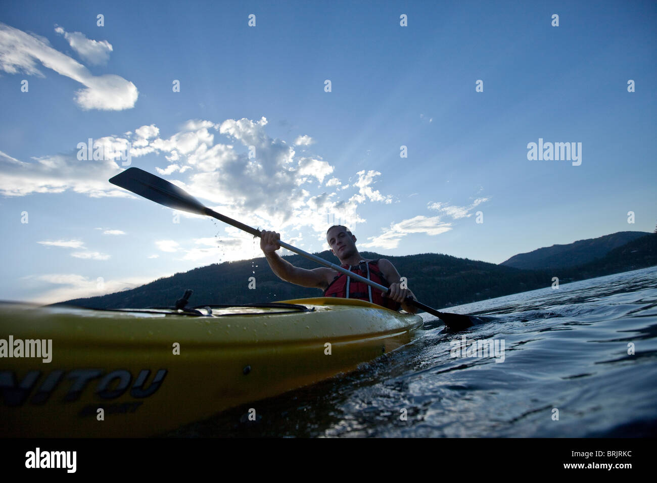 Jeune homme pagaies kayak jaune sur le lac. Photo Stock