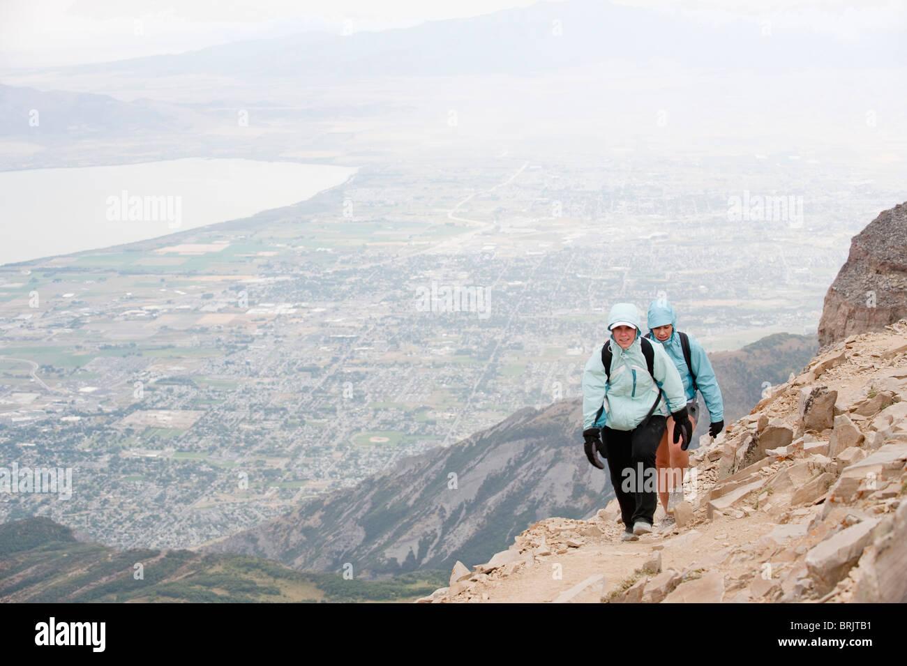 Deux randonneurs près du sommet du Mt. Janie, avec la ville de Pleasant Grove, UT en arrière-plan. Photo Stock