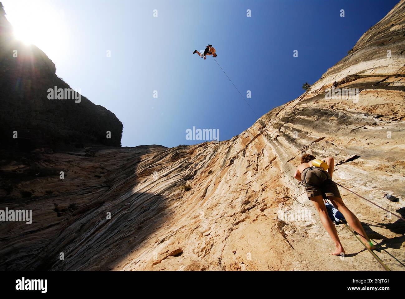 Un grimpeur hors pousse en l'air tandis que la descente en rappel au-dessus d'un autre grimpeur. Banque D'Images