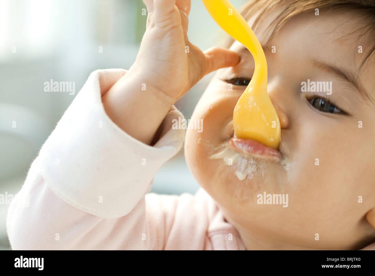 L'alimentation du nourrisson avec cuillère Photo Stock