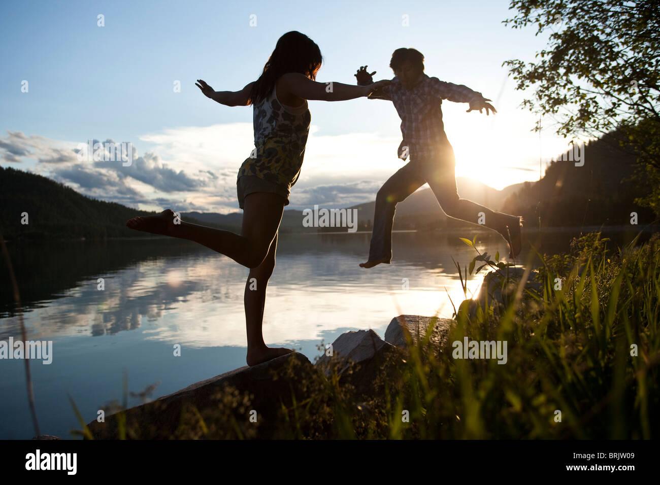 Deux jeunes adultes en équilibre sur des rochers au coucher du soleil à côté du lac. Photo Stock