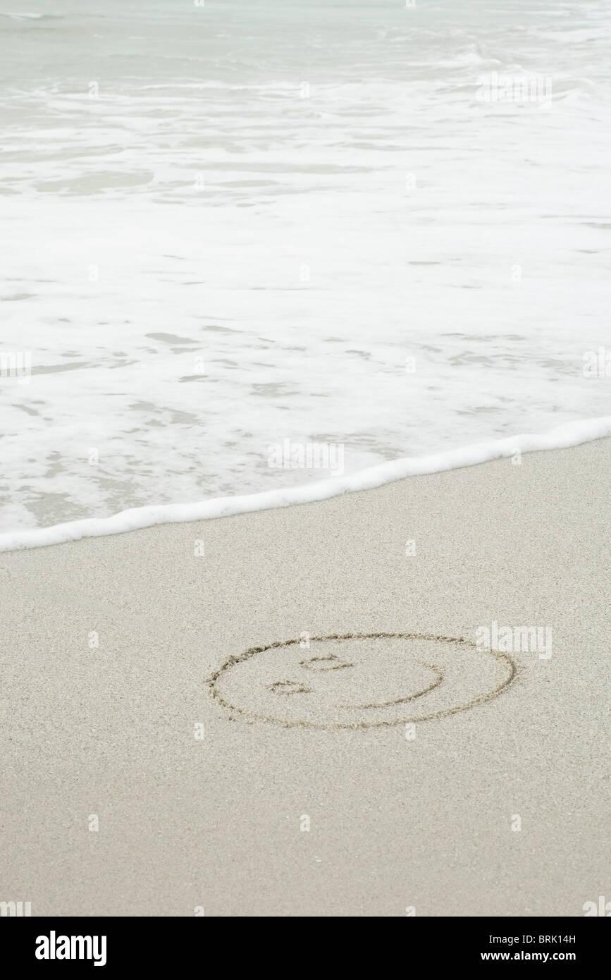 Smiley dessiné dans le sable sur la plage Photo Stock