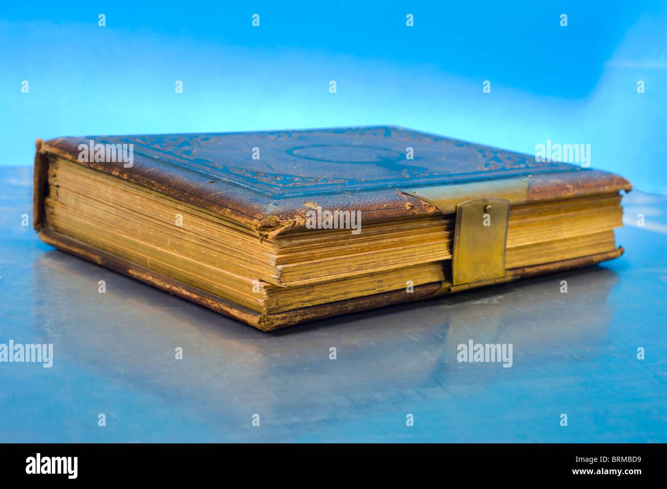 Grand vieux symbole de livre d'or fond bleu symbolique ancienne bible d'or journal lumineux studio shot Photo Stock