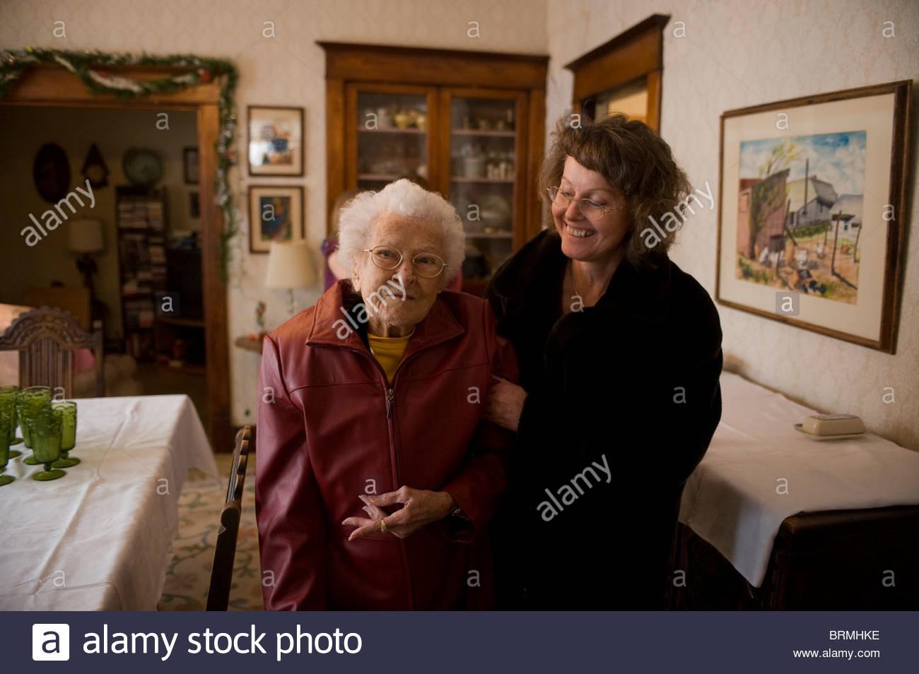Une femme et sa grand-mère arriver à une réunion de famille à Noël. Banque D'Images