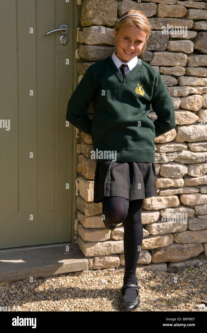 Smiling schoolgirl appuyé contre un mur de pierre Photo Stock