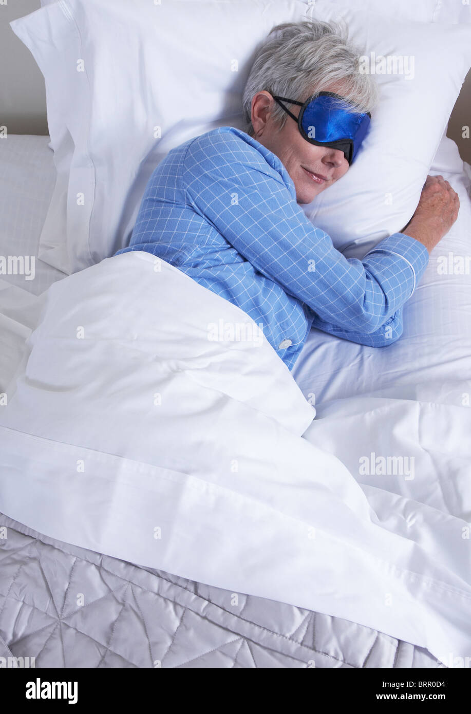 Portrait of young woman wearing sleep mask Lying in Bed Photo Stock