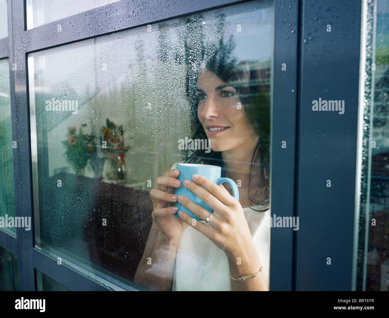 Mid adult woman drinking coffee et regardant par la fenêtre sur jour de pluie. La forme horizontale Photo Stock