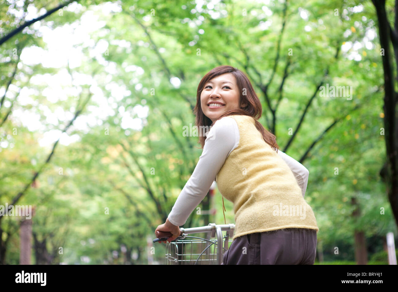 Young woman riding bicycle, smiling Banque D'Images