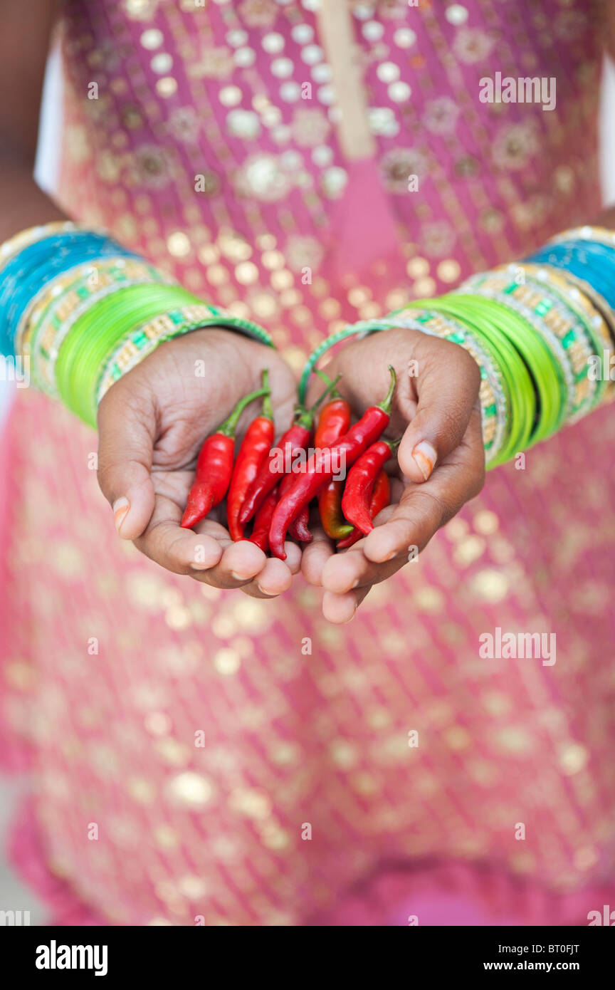 Indian girl holding red chili peppers au creux des mains Photo Stock
