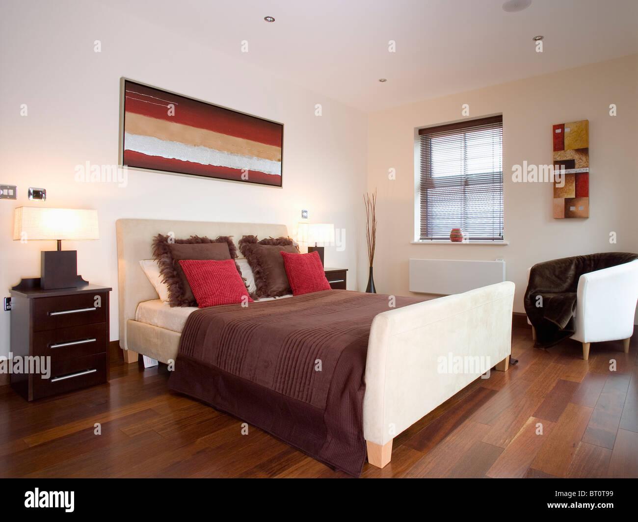 Coussins rouge et marron en daim beige sur meubles lit dans chambre ...
