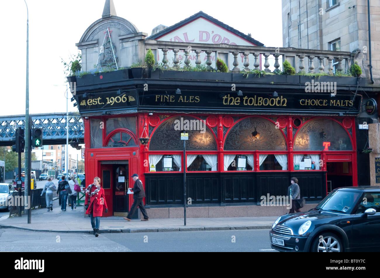 Une femme dans un manteau rouge traversant la rue près de la Pub péage péage (taverne) à Glasgow Photo Stock
