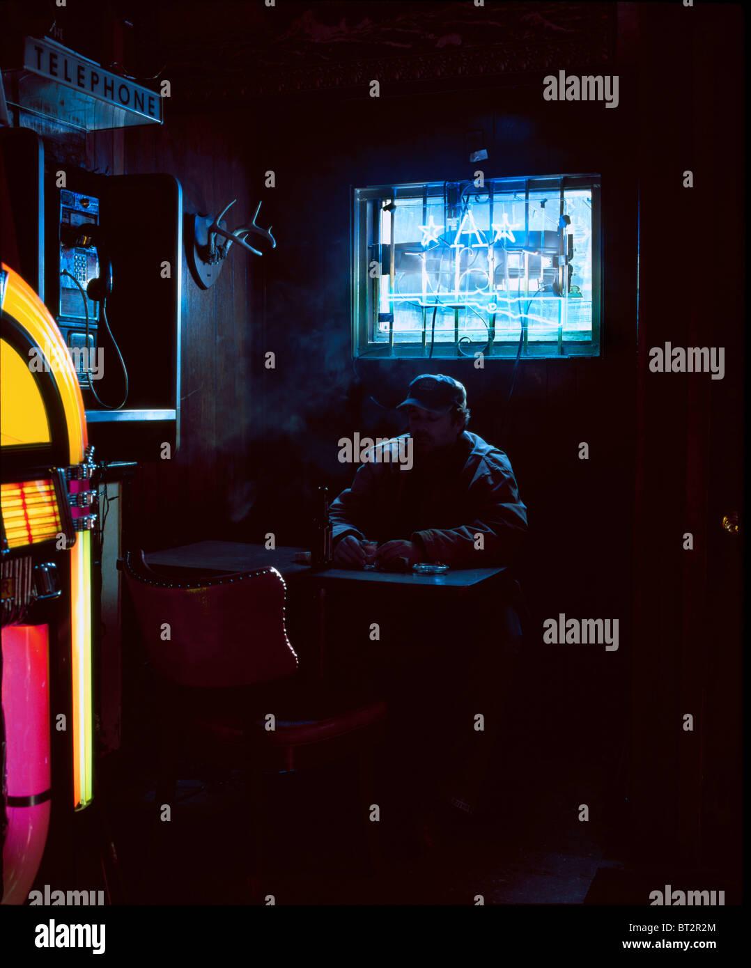 L'homme, l'intérieur du bar, allumé la lumière du jour et des néons, Banque D'Images