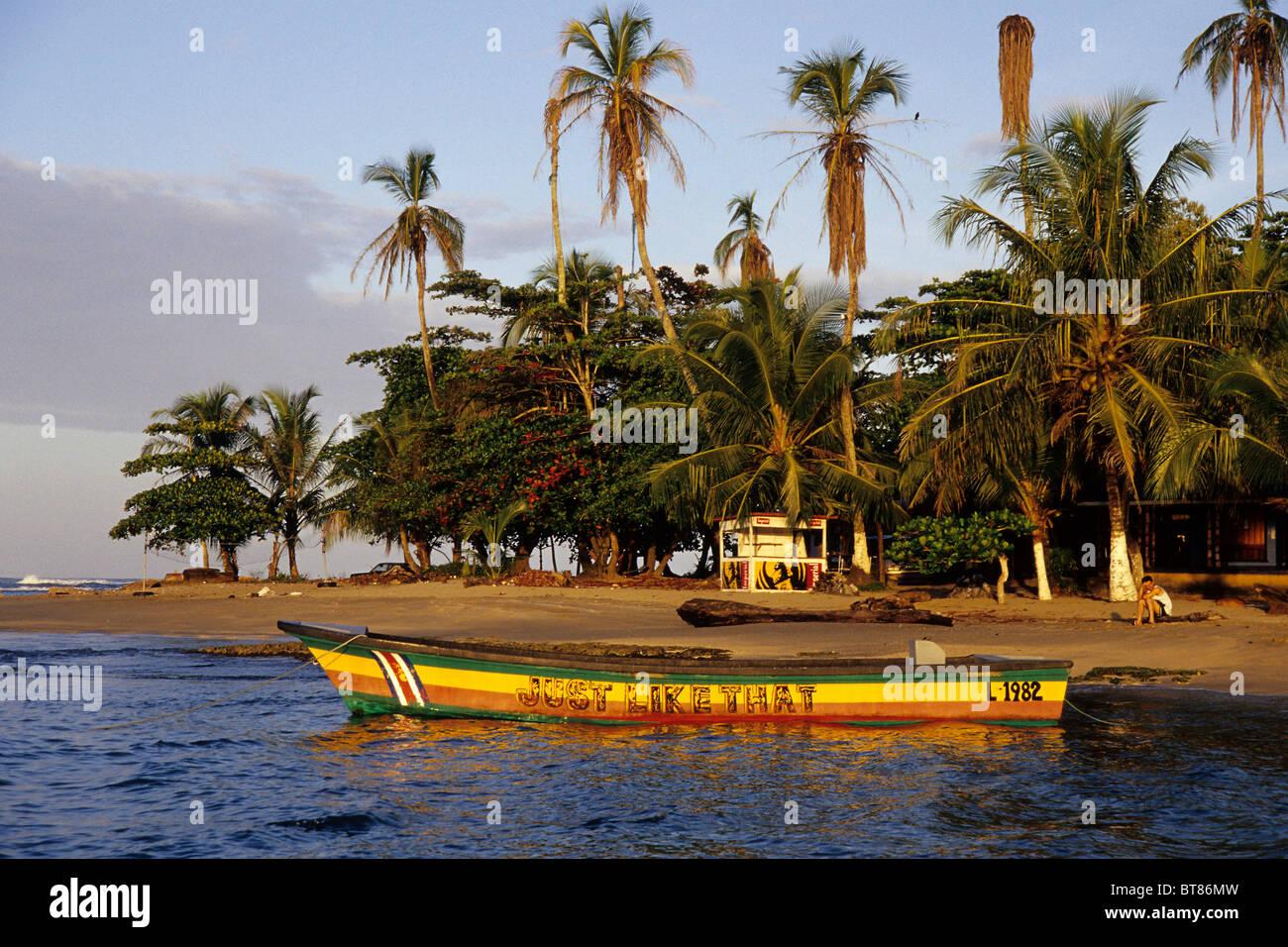 Petit bateau peint en couleurs reggae sur une plage tropicale avec palmiers, Puerto Viejo de Talamanca sur la côte Photo Stock