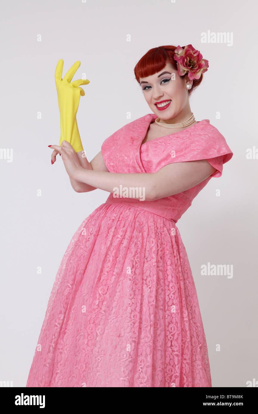 Femme au foyer des années 1950 mise sur un gant en caoutchouc Photo Stock