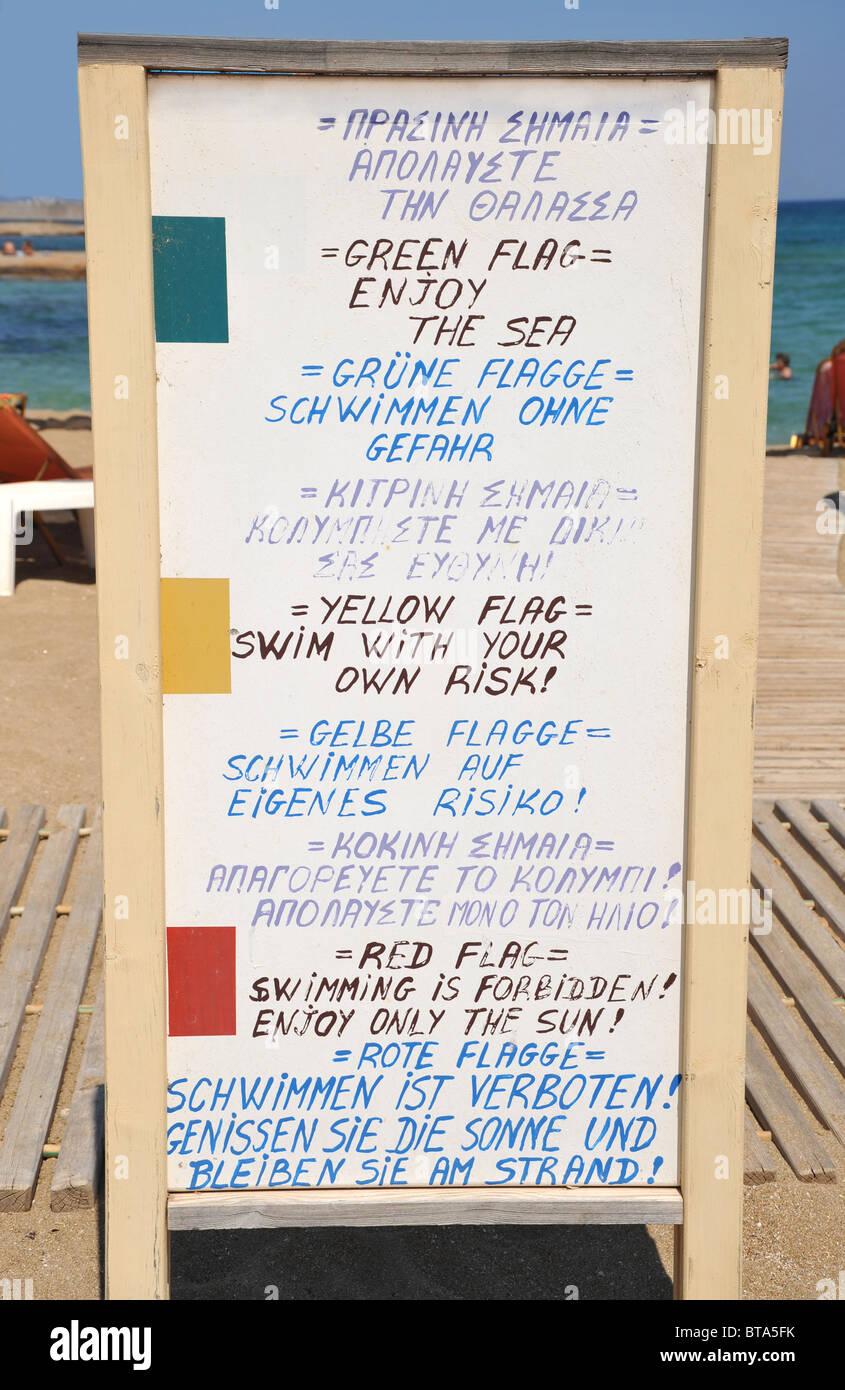 Beach sign en langues allemande et anglaise expliquant les vert, jaune et drapeau rouge natation instructions. Banque D'Images