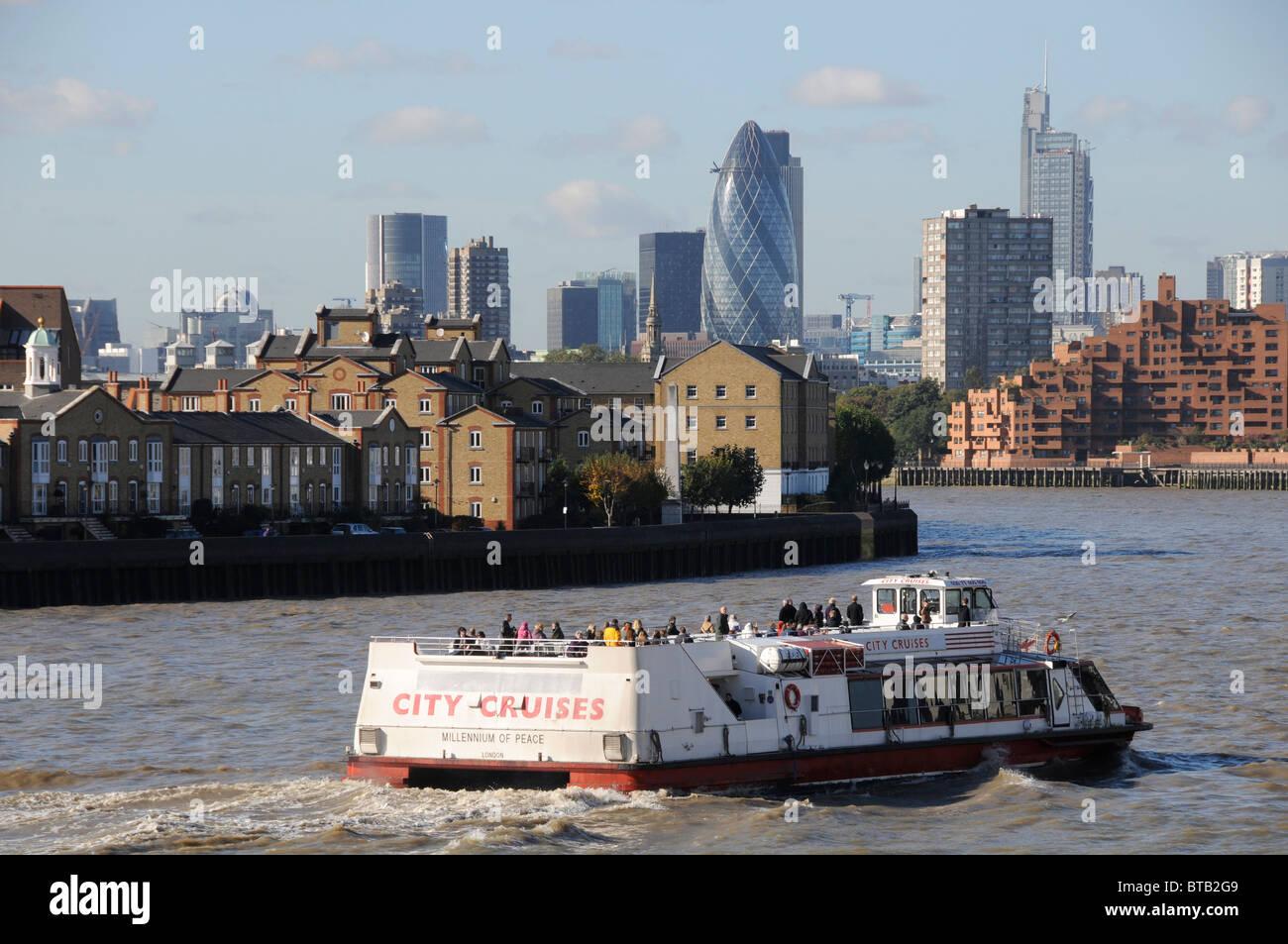 Les touristes EN FERRY LE LONG DE LA RIVIÈRE THAMES AVEC CITY DE LONDRES EN ARRIÈRE-PLAN Photo Stock