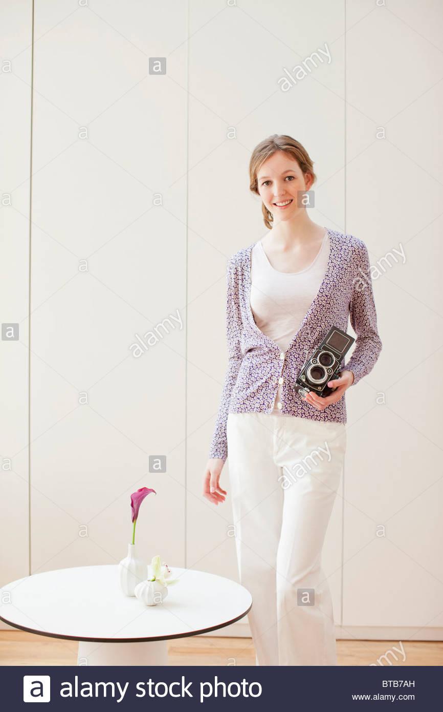 Smiling woman holding retro camera Photo Stock