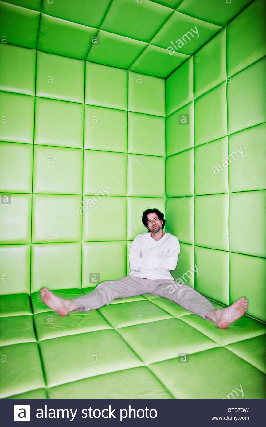 Homme assis avec les jambes dans la chambre capitonnée Photo Stock