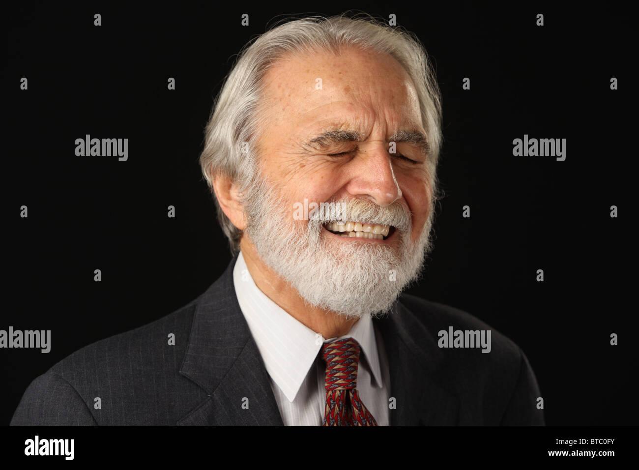 Portrait of laughing, barbu aux cheveux gris senior businessman en costume et cravate, studio shot, fond noir, le Photo Stock