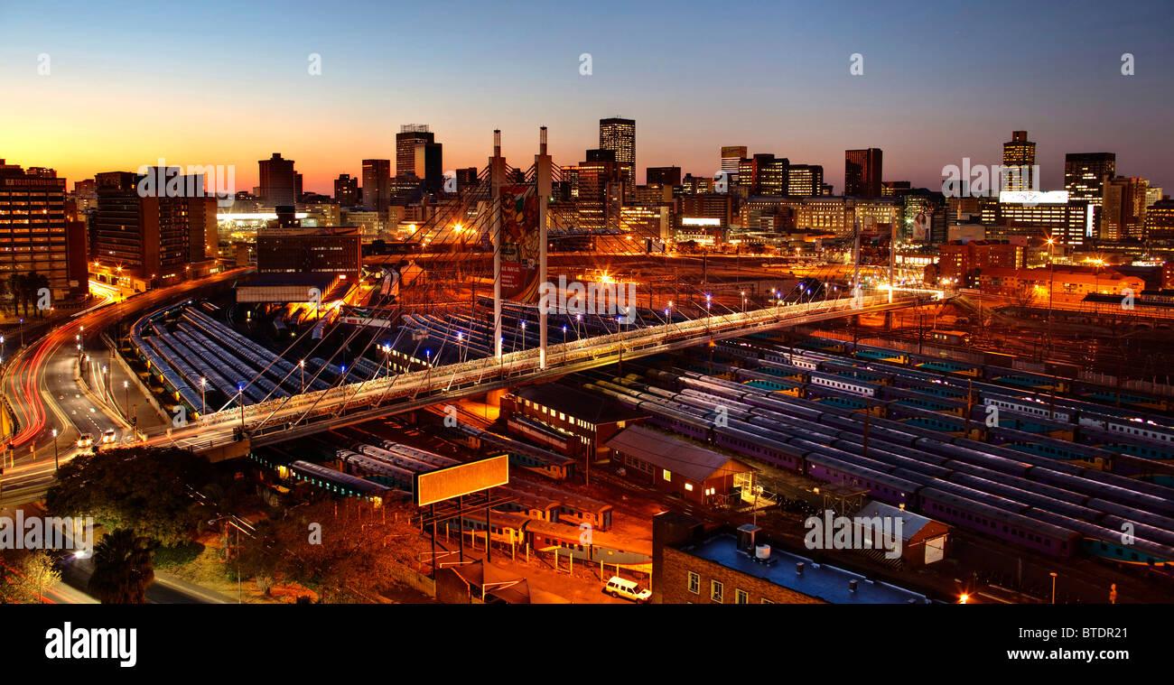 Le lever du soleil sur la ville de Johannesburg avec Nelson Mandela Bridge et les cours de triage de Park Station. Photo Stock