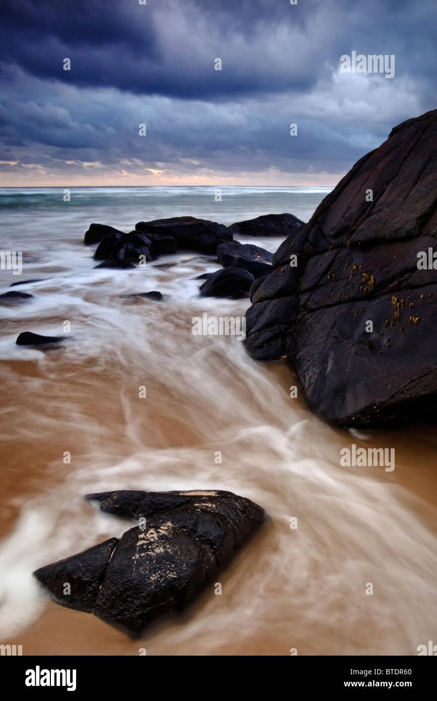 Moody seascape de rochers en premier plan et sombres nuages de pluie Photo Stock
