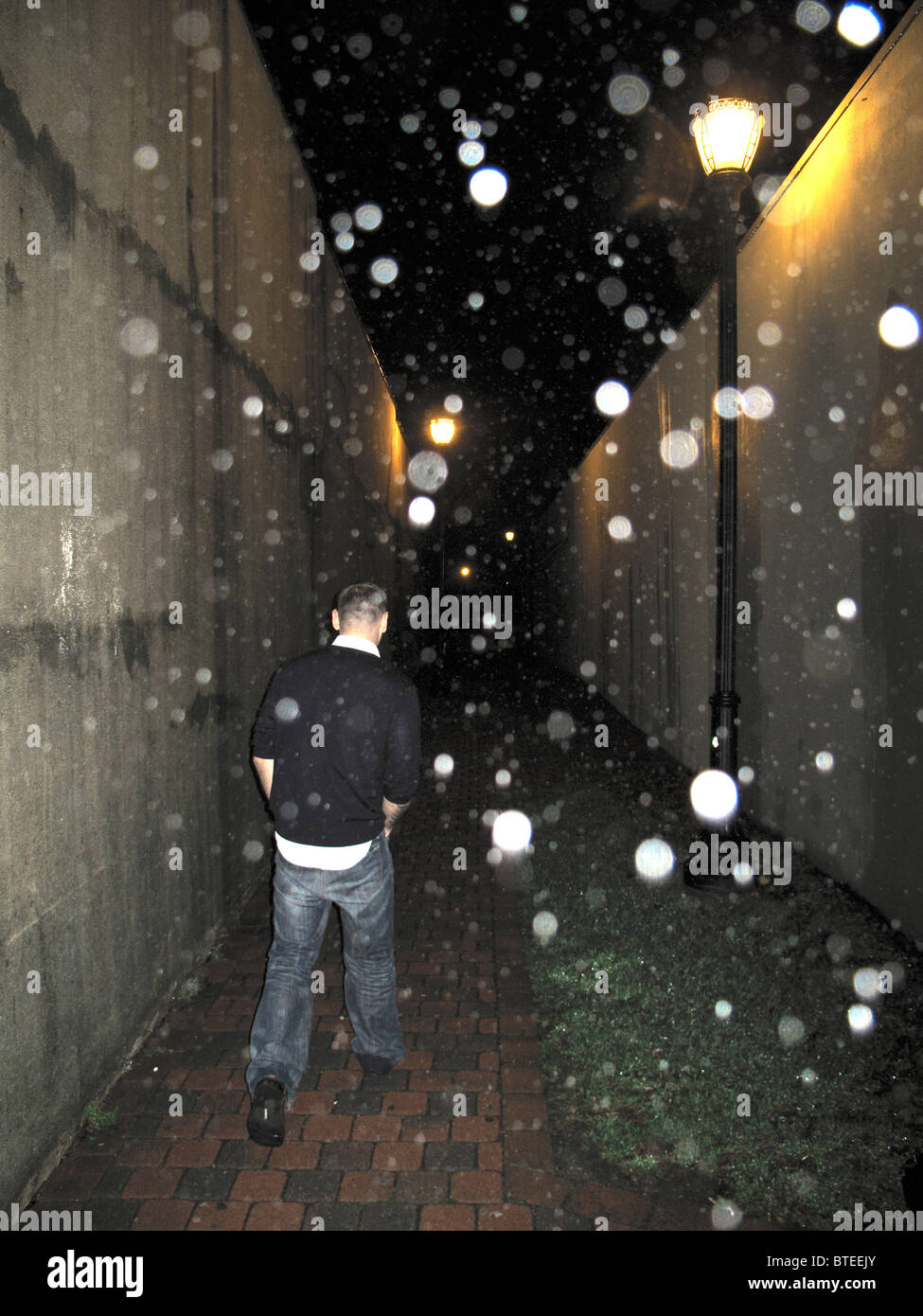 Homme marchant dans la nuit pluvieuse sur ruelle Photo Stock